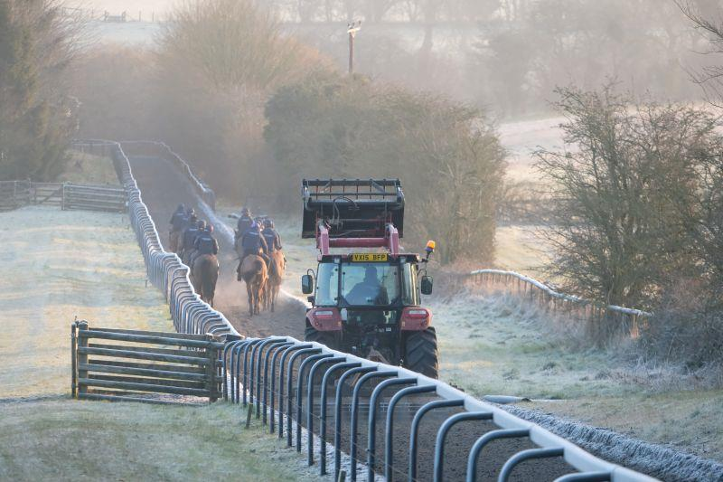 Tractor harrowing the gallop behind the horses