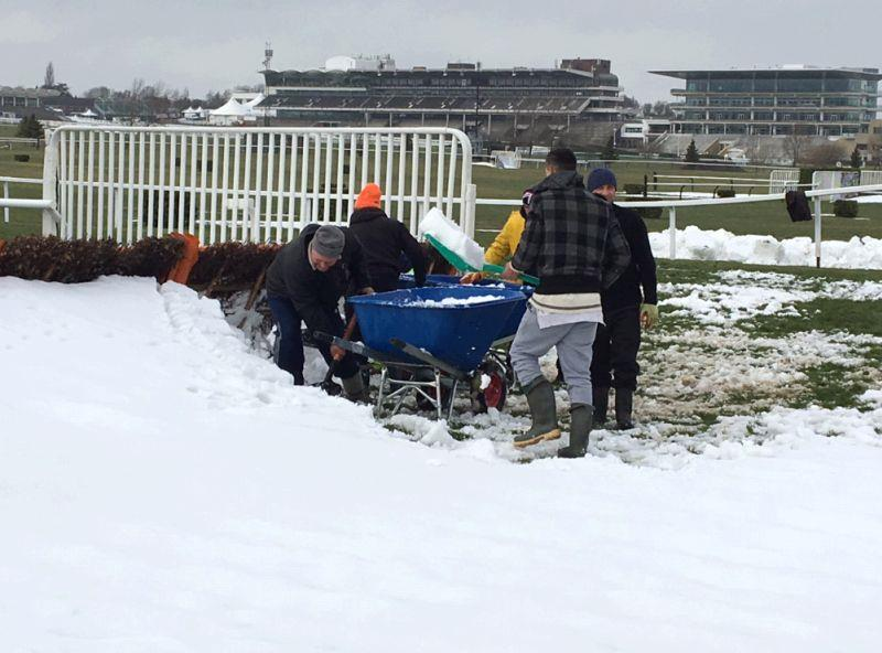The Cheltenham team removing the snow from behind a hurdle