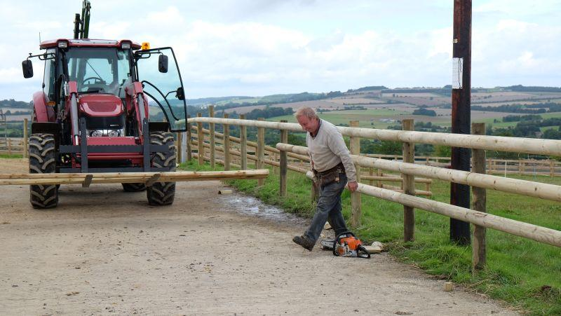 Pete Currill is putting up the new post and rails in front of the top barn.