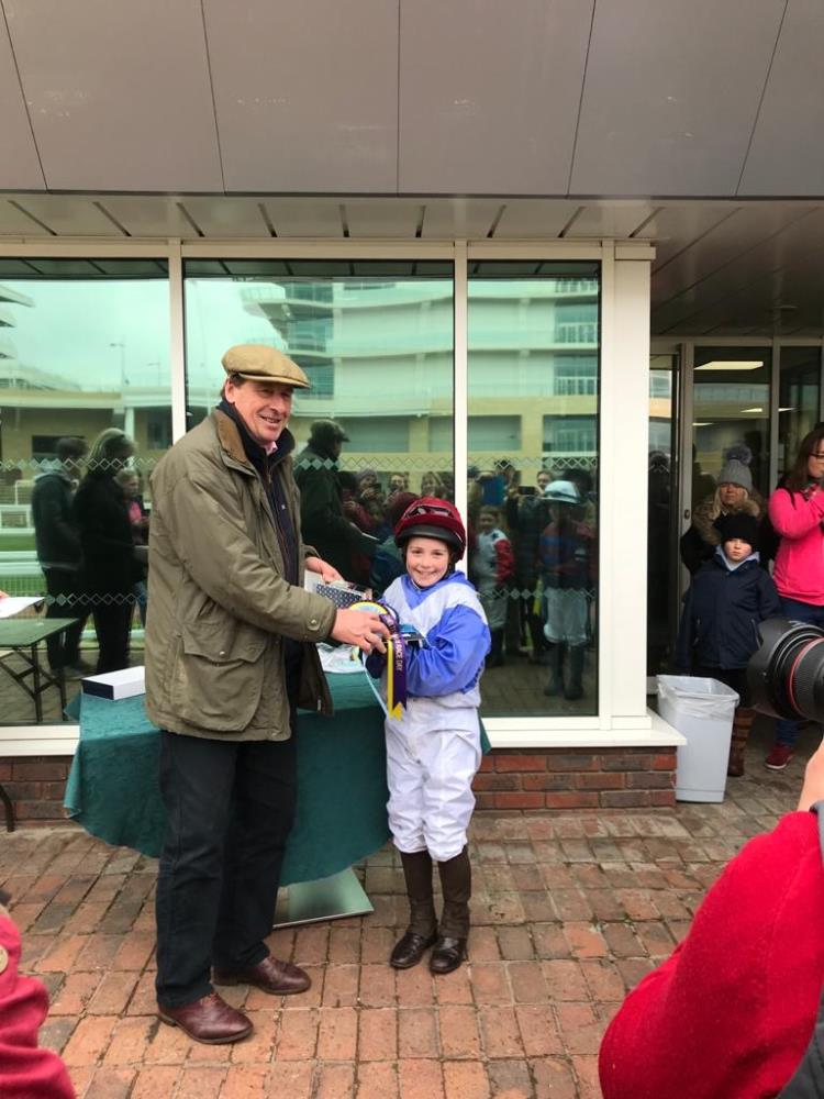 I am presenting Daisy with her pony racing prize at Cheltenham